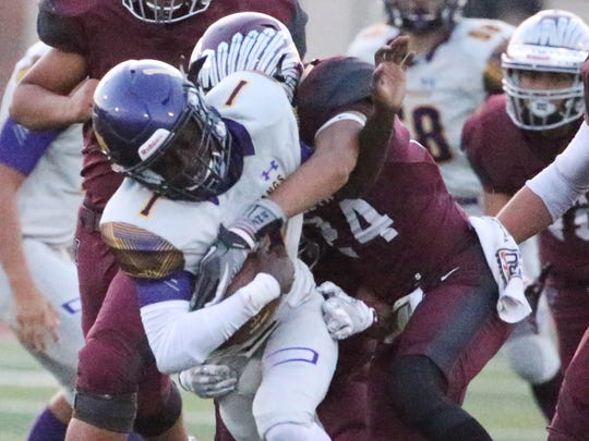 Burges running back Quan Mcneil, center, tries to force his way through the Ysleta defense during a run Friday night at Ysleta. .