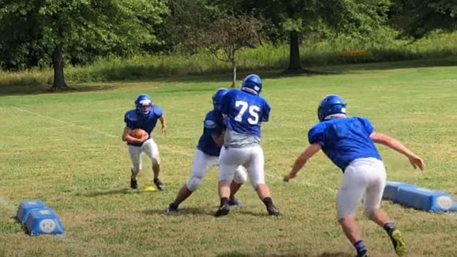 Seneca football players participate in a tackling drill.
