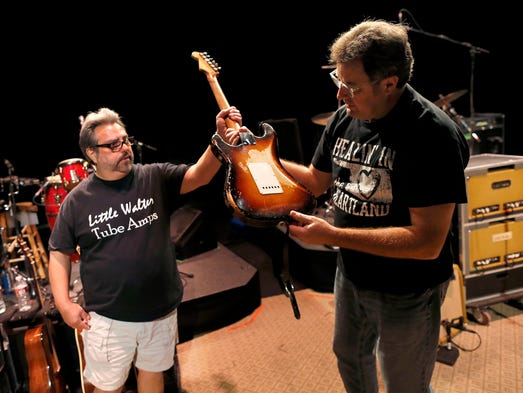 """Guitar technician Vinnie Garcia hands country legend Vince Gill his 1957 Fender Stratocaster after a sound check at the Mesa Performing Arts Center on Oct. 24, 2013. Garcia, who has been best friends with Gill since the seventh grade, sold Gill his first Stratocaster for $200 and a pair of cowboy boots. """"I love the versatility of the guitar as much as anything,"""" Gill said. """"No matter what way you want to try to play it, it always responds."""""""