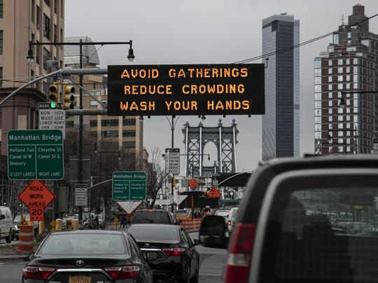 FILE - In this March 19, 2020, file photo, the Manhattan bridge is seen in the background of a flashing sign urging commuters to avoid gatherings, reduce crowding and to wash hands in the Brooklyn borough of New York. The coronavirus pandemic is leading to information overload for many people, often making it difficult to separate fact from fiction and rumor from deliberate efforts to mislead. (AP Photo/Wong Maye-E, File)