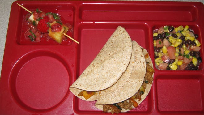 Whole wheat soft tacos filled with pork, apples, carrots and Swiss chard are pictured with a side of black bean, corn and tomato salsa tossed in an apple cider-cilantro vinaigrette and a dessert of fruit kabobs topped with a strawberry-mint glaze. This meal was designed and cooked by a team of fifth grade sous chefs at L. Leo Judice Elementary led by Chef Mindy Prados of Joey's.