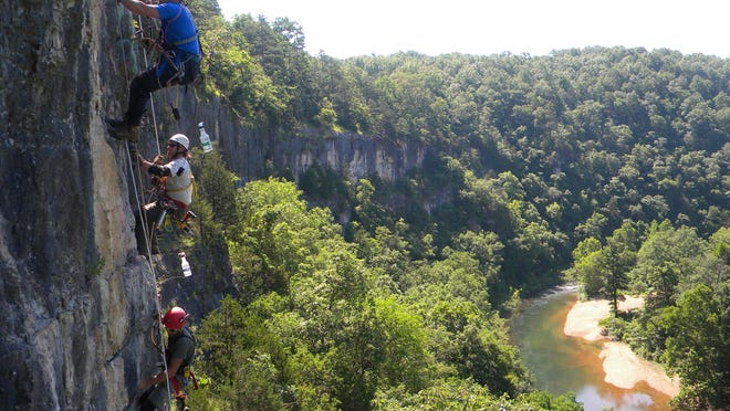 Tony Schmitt, Dan Lamping, and Joe Sikorski from the Cave Research Foundation hang from ropes while cleaning off spray-painted graffiti from a cliff high above the Jacks Fork River.