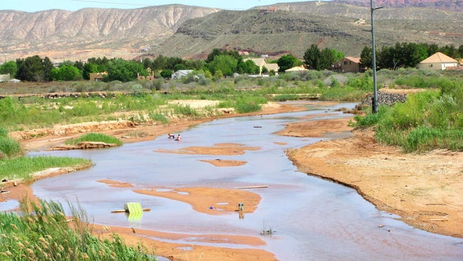 The shallow waters of the Virgin River flow through central St. George on Sunday, April 5, 2015.