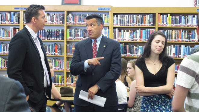AP Nevada Gov. Brian Sandoval talks to Reno High School principal Kris Hackbusch while pointing to his own daughter, Maddy. Nevada Gov. Brian Sandoval talks to Reno High School principal Kris Hackbusch while pointing to his own daughter, Maddy, before signing into law on Monday, June 8, 2015, a measure creating millions of dollars in incentives to combat the state's teacher shortage in Reno, Nev. (AP Photo/Scott Sonner)