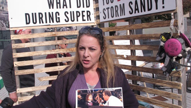 Kelly Brier of Middletown, N.J. holds a photo of her daughter Nicole speaking with New Jersey Gov. Chris Christie at a town meeting several months after her home was destroyed by Superstorm Sandy, on Tuesday, Oct. 27, 2015, in Trenton, N.J. Sandy victims who either still are not back in their homes or just recently got back tried to pitch tents across from the Statehouse in Trenton Tuesday to dramatize their plight but were prevented from erecting the tents by State Police. (AP Photo/Wayne Parry)