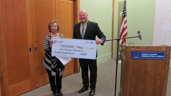 Edward Bergstraesser of AT&T presents a $2,500 contribution to Betsy Kopstein-Stuts, Catharine Street Community Center's board president.