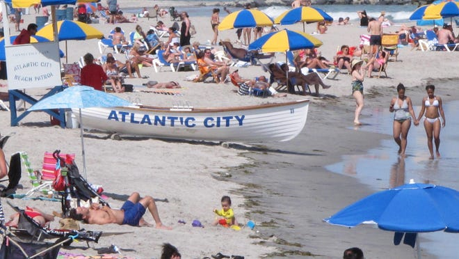 This June 23, 2014 photo shows beachgoers on the Atlantic City, N.J., beach. New Jersey Gov. Chris Christie, Senate President Stephen Sweeney and Atlantic City Mayor Don Guardian announced a plan to give the state sweeping powers over municipal finances Tuesday. (AP Photo/Wayne Parry)