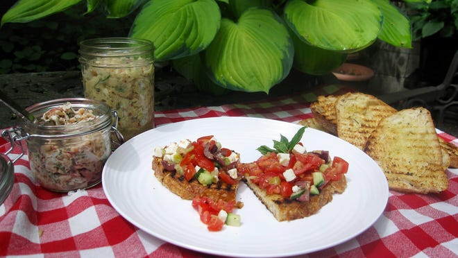 Salmon salad in a jar, left, sits next to the white bean salad and chopped greek salad on grilled bread.