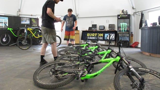 Ry Wolfel, a bike mechanic with East Burke Sports, inspects rental bikes in East Burke. Burke Mountain Resort has reopened for the mountain biking season.