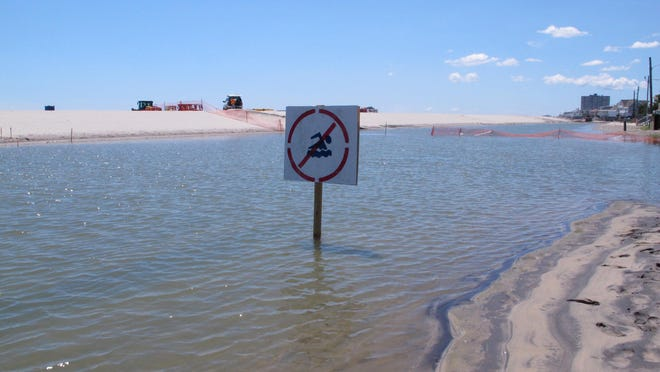 A no swimming sign in one of numerous large pools of water that have formed on the beach in Margate due to heavy rains. The water is blocked from draining into the ocean by new sand dunes being built as part of a storm protection program that Margate residents vigorously fought, claiming that the dunes would cause exactly the type of standing water that has occurred.