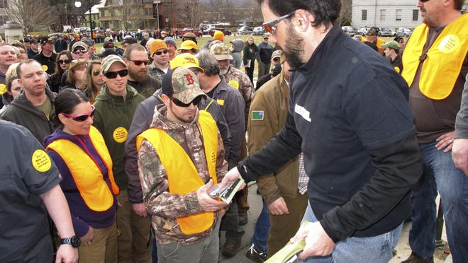 Rob Curtis, executive editor of a firearms magazine, hands out 30-round magazines at a gun rights event outside the Vermont Statehouse in Montpelier, Vt., on Saturday, March 31, 2018, to oppose gun restriction legislation passed by the Legislature the previous day.