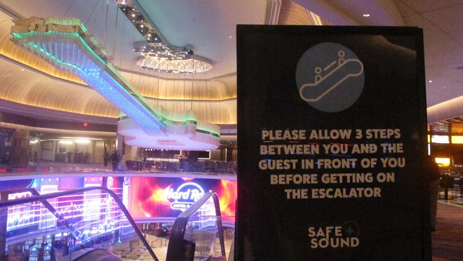 A sign in the Hard Rock casino in Atlantic City, New Jersey, instructs customers to maintain distance on the escalator to prevent the spread of the coronavirus. Smoking, drinking and indoor eating will all be prohibited when Atlantic City's casinos reopen after being shut for three months due to the coronavirus outbreak under rules imposed by New Jersey Gov. Phil Murphy on June 29, 2020.