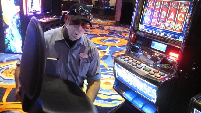 This June 3, 2020 photo shows a worker at the Ocean Casino Resort in Atlantic City N.J. removing the chair from a slot machine, part of distancing measures to help prevent the spread of the coronavirus. On June 22, New Jersey Gov. Phil Murphy announced that Atlantic City's nine casinos may reopen on July 2 at 25% of capacity.