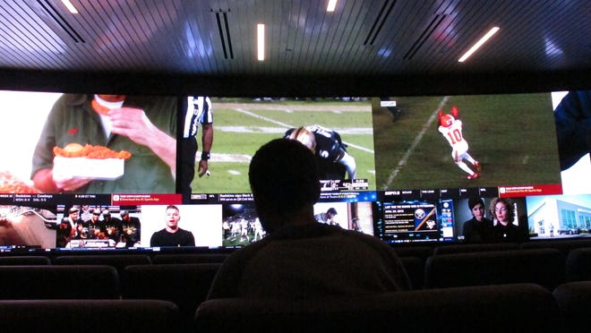 A customer watches video screens at the sports betting facility at Resorts Casino in Atlantic City, N.J. The Rivers Casino in Pittsburgh was testing sports betting Thursday and possibly open during regular betting hours, barring issues, on Saturday.