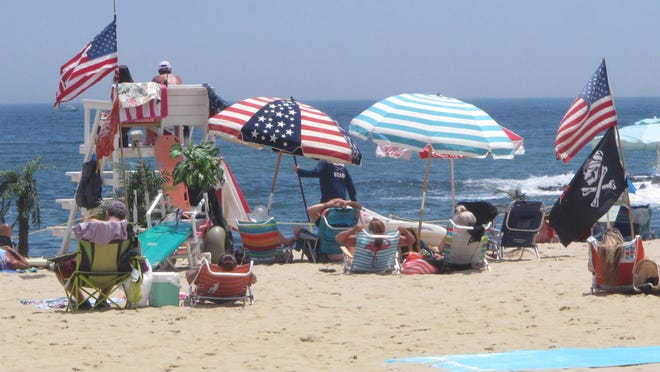 Flags line the beach in Belmar, N.J on June 28, 2020. With large crowds expected at the Jersey Shore for the July Fourth weekend, some are worried that a failure to heed mask-wearing and social distancing protocols could accelerate the spread of the coronavirus.