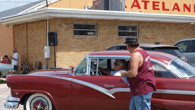 Dave Sabin of Dearborn Heights, a member of Downriver Wanderers Car Club, holds 50/50 tickets while directing a driver to a parking spot Saturday for the car show at Dixie Skateland.