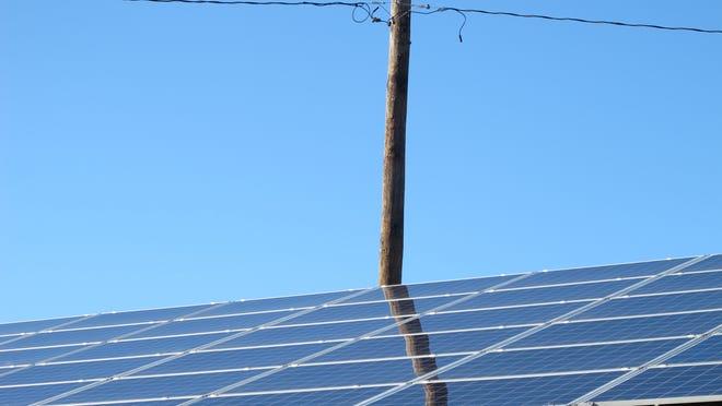 A power line and net-metered solar panel deck the Burlington skyline.