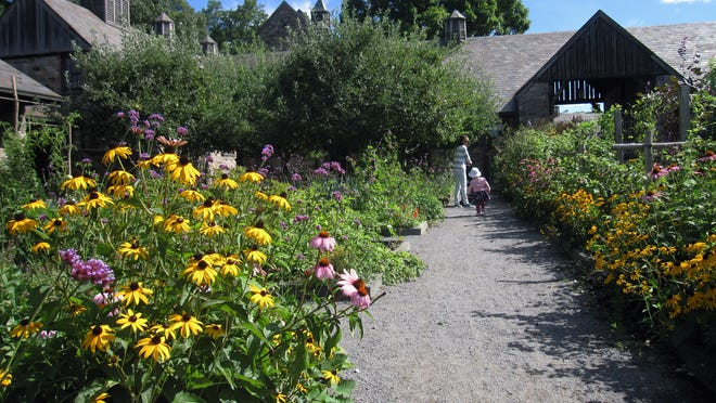 Visitors walk through a flower garden at Stone Barns, a nonprofit working farm in Pocantico Hills, N.Y., dedicated to education and conservation. Stone Barns belonged to the Rockefeller family and was turned into an education site by David Rockefeller in honor of his late wife Peggy, an advocate for farmland preservation. Visitors can see organic gardens, greenhouses, free-range turkeys and chickens, a barn full of piglets, fields of vegetables, and a buzzing apiary.