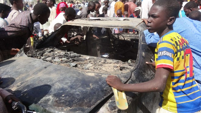 Residents look at a burnt car outside the central mosque in northern Nigeria's largest city of Kano on Nov.29, 2014, a day after twin suicide blasts hit the mosque during weekly Friday prayers.