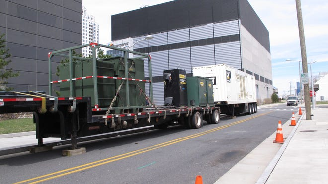 Portable generator trucks sit on a street alongside the former Revel casino in Atlantic City, N.J., Wednesday April 15, 2015. Inspectors from the New Jersey Department of Environmental Protection determined on Wednesday that the generators would probably not meet federal pollution standards and urged the casino's new owner to find newer, cleaner ones before they would be allowed to be started up. (AP Photo/Wayne Parry)