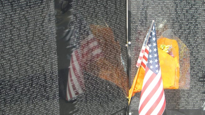 """An American flag is reflected in the panels of the traveling Vietnam Memorial replica known as """"The Wall That Heals"""" on Saturday. The exhibit will leave its Washington City location Sunday afternoon."""