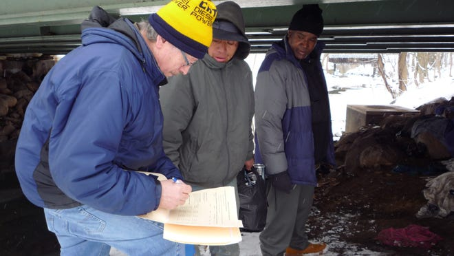 John Fella of the Rockland County Department of Social Services take notes during his visit to a homeless encampment under the Lawrence Street overpass in Spring Valley.