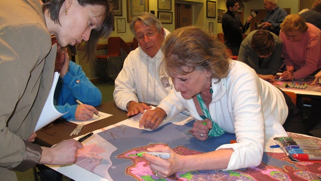 Darlene Greene (left) reviews maps of Toms River N.J., that show flooding damage from Superstorm Sandy with Jeff Coley and Jo-Ann Herbst.