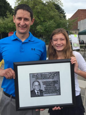 """Matt Elstro and his daughter, Ainesleigh Elstro, 12, hold an image of the plaque that will honor Matt's grandfather, Howard """"Jack"""" Elstro, in a new park being named for him. The park is being built in the first first block between North Sixth and Seventh streets in Richmond. The elder Estro served on the Richmond Common Council for 47 years before his death in July 2014."""