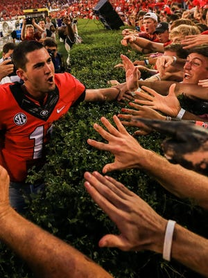 Georgia quarterback Aaron Murray celebrates with fans at Sanford Stadium after the Bulldogs edged LSU.