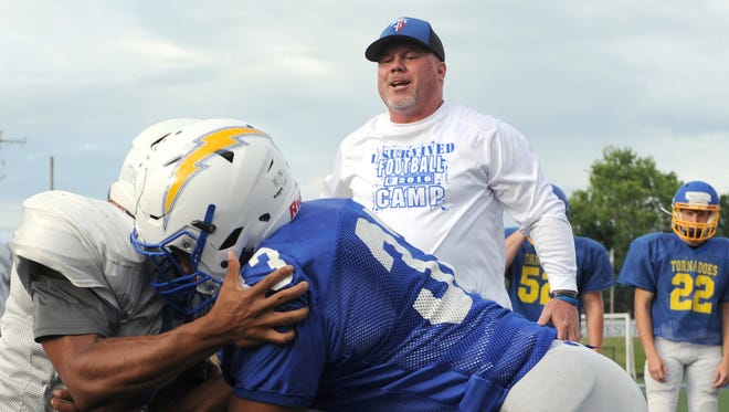 Head Coach Chad Grandstaff cheers on Zanesville's Leo Crosby and Deaunte Goins during blocking drills at a Muskingum Valley All-Stars practice Thursday in Zanesville.