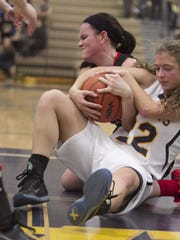 Pinckney's Dakota Selmi (background) battles for a loose ball with Hartland's Michelle Moraitis. Both seniors have been varsity players since they were freshmen.
