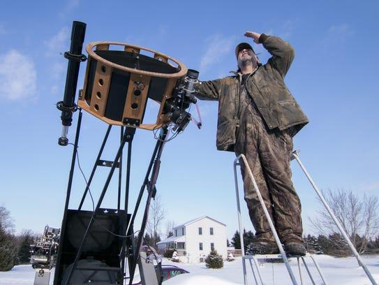 Standing next to a telescope he built, amateur astronomer