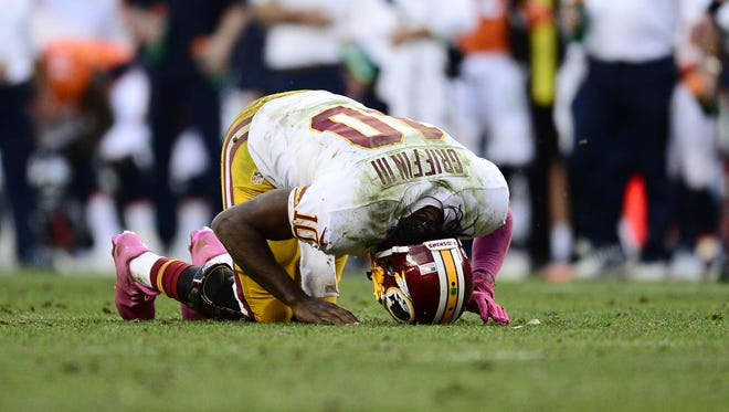 Washington Redskins quarterback Robert Griffin III (10) lays injured after a sack by Denver Broncos defensive tackle Terrance Knighton (94) (not pictured) in the fourth quarter at Sports Authority Field at Mile High.