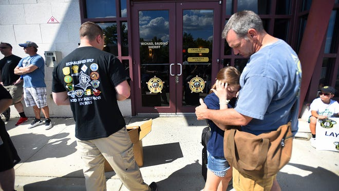 Peter Flannery (R) who lost his job as a Bergen County Patrol Officer and Bomb Tech after 6 and half years, receives a hug from his daughter Stella (age 10) while waiting his turn to in his gear at B.C.I (Bureau of Criminal Investigation) on South River Street in Hackensack.