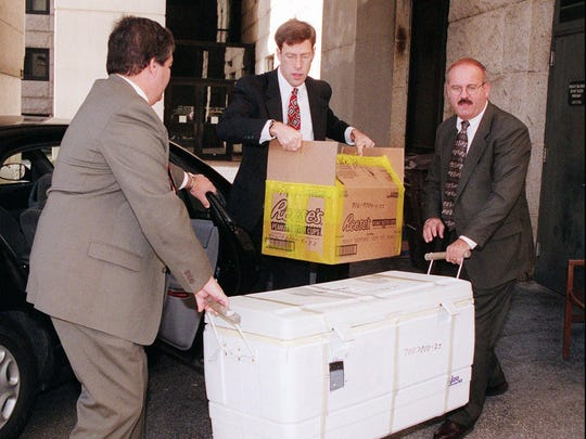 FBI detectives carry evidence for the Thomas Capano murder trial into the courthouse in Wilmington, Del., Wednesday, Dec. 2, 1998. Prosecutors say Capano dumped the body of Anne Marie Fahey at sea in the cooler. Ken Chubb and his family were fishing about 10 miles off the Delaware coast when his son noticed a cooler bobbing in the waves. The 162-quart cooler had a pinkish stain at the bottom and a bullet hole in it.