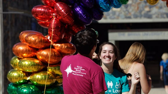 Duke freshman Kira Panzer, right, and senior Duncan Dodson dance during the university's Coming Out Day celebration on Thursday, Oct. 9, 2014 in Durham, N.C.  Lesbian, gay, bisexual and transgender employees and students and allies gathered as a symbol of support in recognition of National Coming Out Day.  (AP Photo/The Herald-Sun, Christine T. Nguyen)