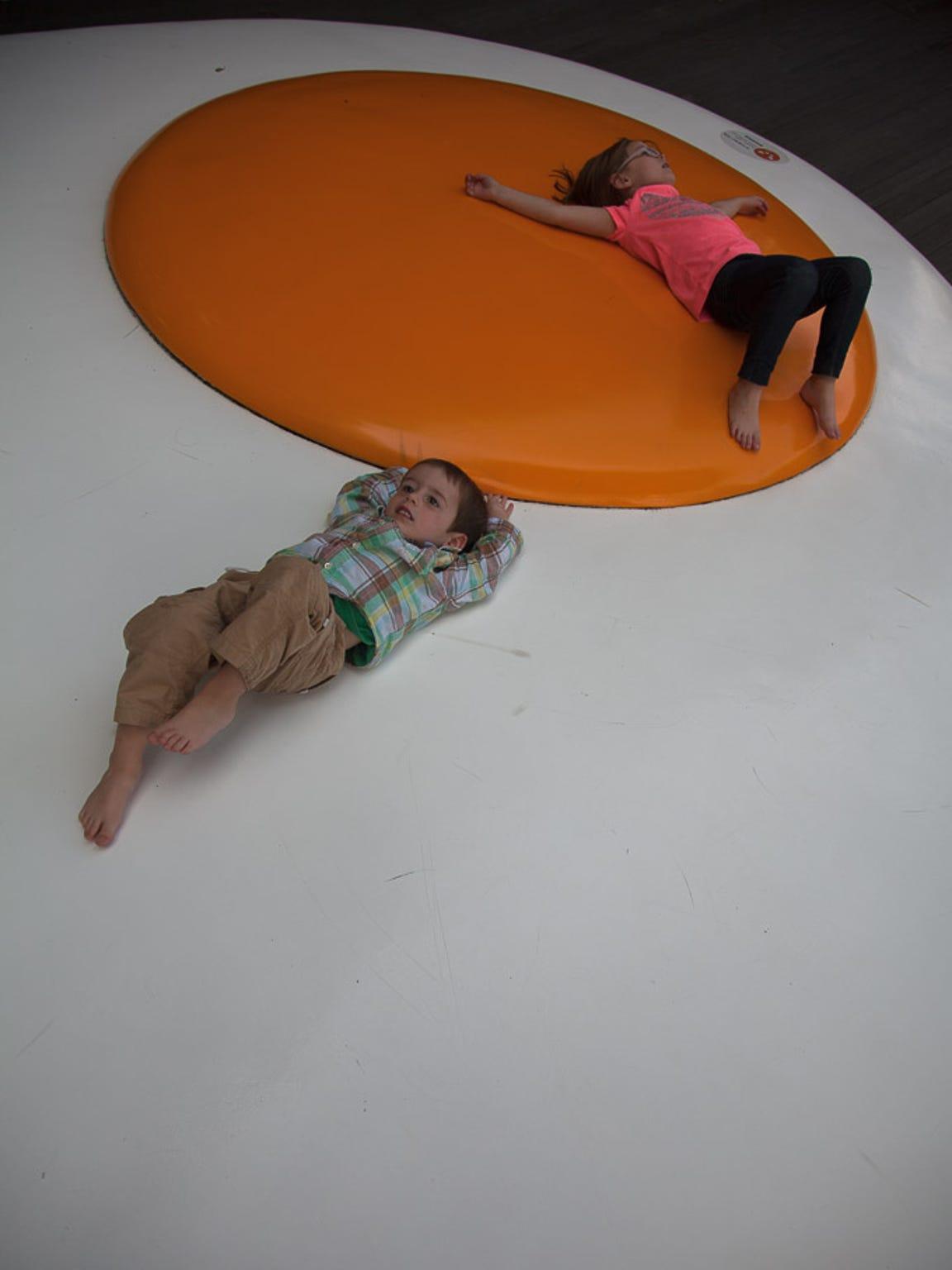 Harper and Walker Hughey relax on an egg sculpture