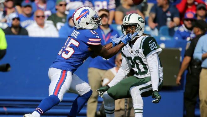 Bills punt returner Brandon Tate fields a kick in front of Jets Marcus Williams.