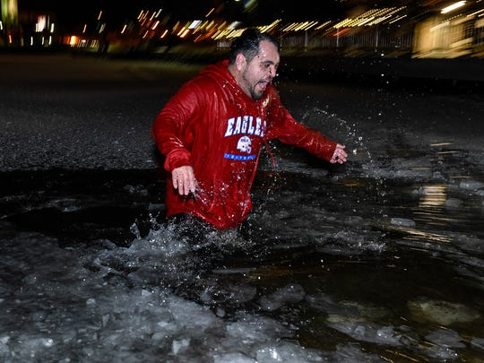 Rob Lopez-Sanchez comes up after submerging himself in Lake George Friday, Dec. 9, during the Pub, Run, & Plunge which is part of the Winter Nights & Lights Festival.