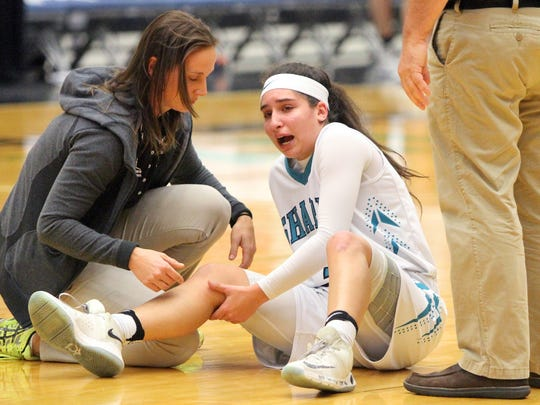 Gulf Coast Rathletic trainer Christina Chirco aids Mya Giusto on the court as they play Winter Haven during the FHSAA 8A girls basketball semifinals Friday February 24, 2017 in Lakeland, Florida. Giusto was out the rest of the game from the injury. Gulf Coast lost the match 41-68. Photos by Cindy Skop 2017