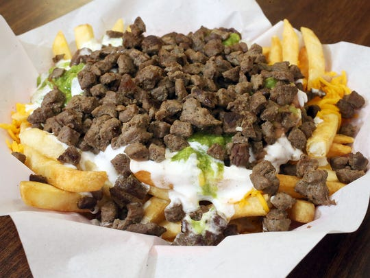A platter of carne asada fries includes cheese, beans, sour cream and guacamole at Rivas Taco Shop at 1342 N. Zaragoza Road.