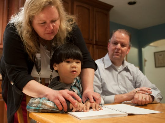 Faye Corman assists her 7-year-old visually impaired son Jon Paul in reading Braille, as Faye's husband and Jon Paul's father Mike Corman, a blind attorney who is fluent in Braille, sits close-by in their Barrington home. Jon Paul, who has only one eye, and significantly limited vision, is learning how to read and write using Braille. 02.23.15