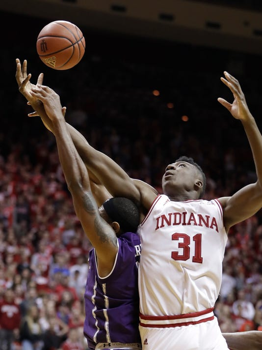 Indiana's Thomas Bryant grabs a rebound over Northwestern's Dererk Pardon during the second half of an NCAA college basketball game Saturday, Feb. 25, 2017, in Bloomington, Ind. Indiana defeated Northwestern 63-62. (AP Photo/Darron Cummings)