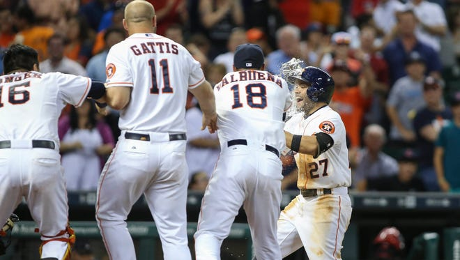 Houston Astros second baseman Jose Altuve (27) celebrates with teammates after hitting a walk off home run during the ninth inning as the Astros defeated the Boston Red Sox 5-4 at Minute Maid Park.