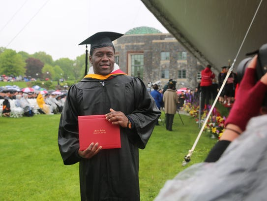 Willie Barrett holds up his degree for a photo Saturday.