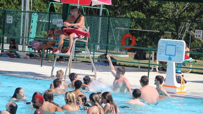A lifeguard observes activities at the Durant city pool last week as a crowd of youths splash in the water. The pool opened earlier this month and is offering swim lessons through July.