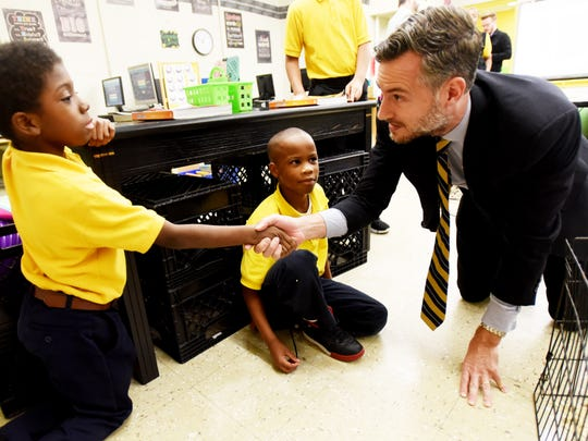 Louisiana state superintendent of education John White talks to Demontrell Davis, left, and Eric Perot at Midway Elementary Professional Development School Wednesday afternoon while visiting several schools.