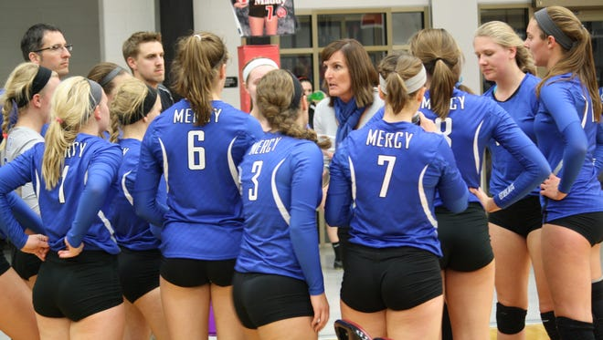 Mercy coach Denise Harvey, middle, addresses her team during the first set of match against Oak Hills Oct. 9, 2014.