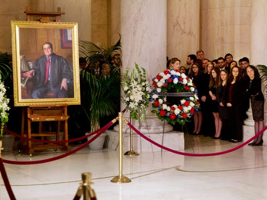 Law clerks and Supreme Court staff watch a private ceremony in the Great Hall of the Supreme Court where the late Justice Antonin Scalia lies in repose on Feb. 19, 2016.