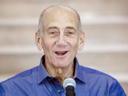 Former Israeli Prime Minister Ehud Olmert speaks to the media after hearing the verdict in his trial on July 10, 2012, in Jerusalem's District Court.